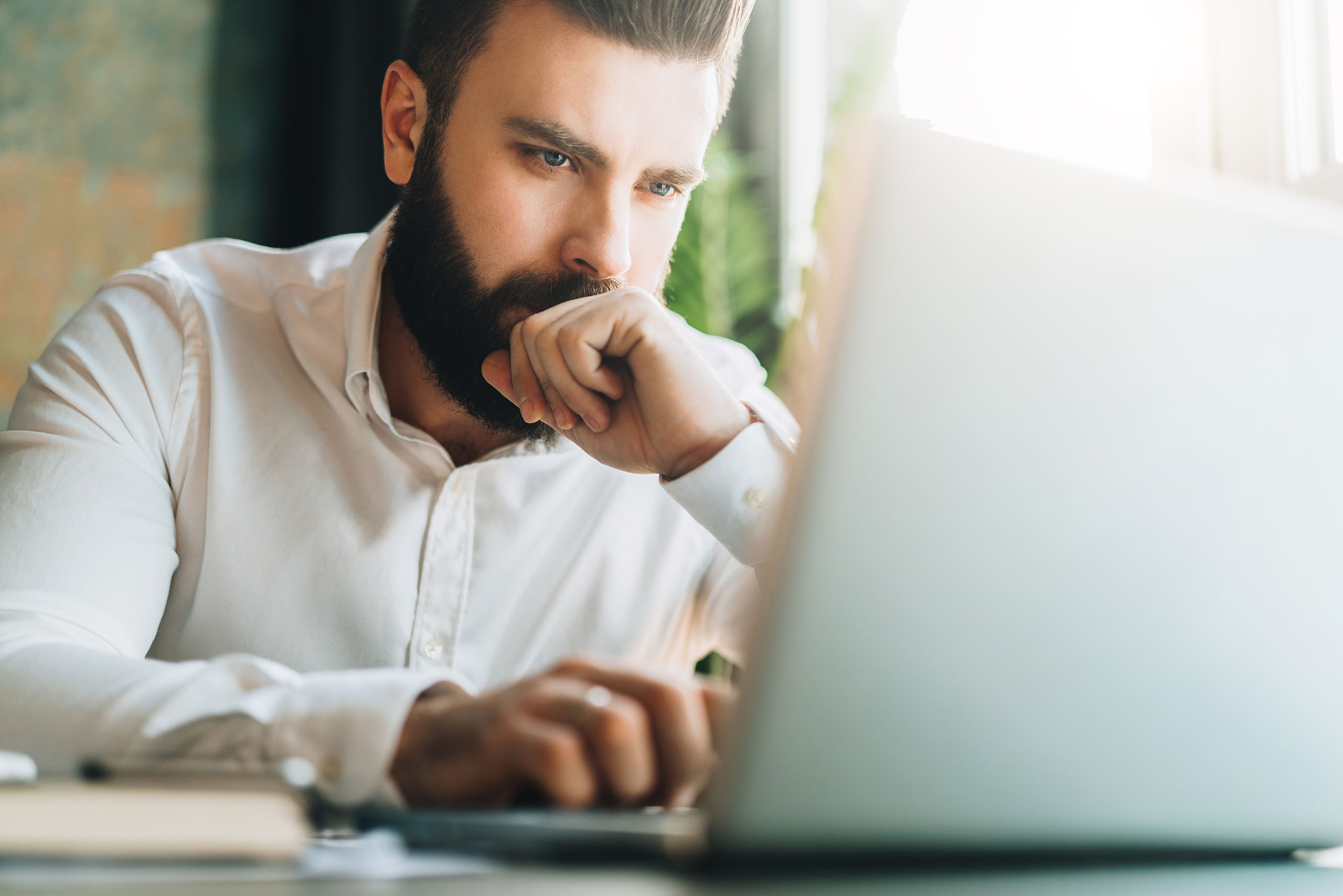 Man looks at laptop concentrating