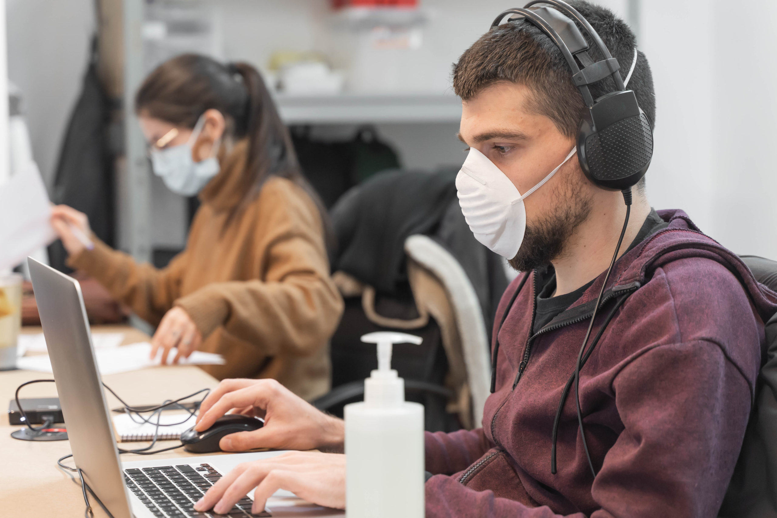 Two workers in an office wearing face masks.