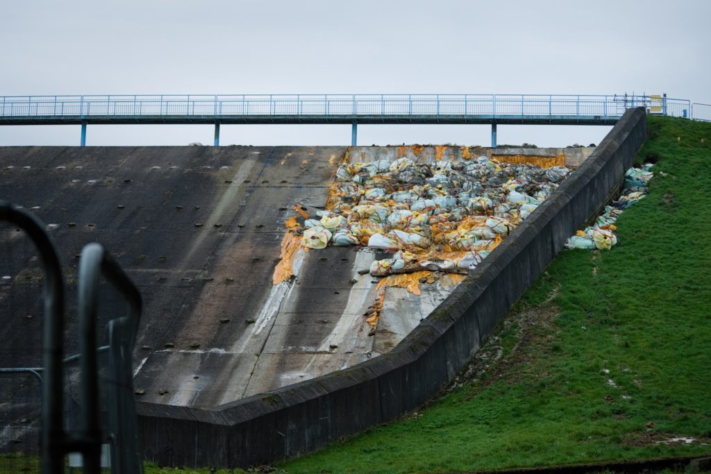 An image of the damage to the spillway in Toddbrook Reservoir. The gap is filled with 400 tonnes of sandbags and the partial grassy hill area has sandbags to stop the water from spilling over the side.